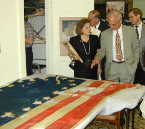 In this photograph from 2001, then-director of the Department of Archives and History Elbert R. Hilliard discusses the recently acquired 20-Star United States flag with former Old Capitol Museum of Mississippi History director Donna Bailey Dye.